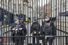 Tung säkerhetsnärvaro framme av kontoret för premiärminister` s på 10 Downing Street i staden av Westminster, London, England, Arkivbilder