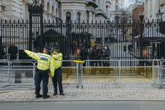 Tung säkerhetsnärvaro framme av kontoret för premiärminister` s på 10 Downing Street i staden av Westminster, London, England, Arkivfoto