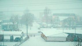 Tung snö som faller i vinter på en väg av lilla staden arkivfilmer