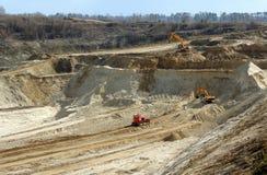 Tunga grävskopor och bulldozerarbeten in i industriell sand bryter sten Arkivfoto