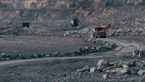 Tunga lastbilar bär stenen i villebrådet som bryter granit arkivfilmer