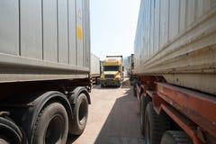 Tunga lastbilar laddade med godssläp som parkerades i väntande område på statsgränskorsning i Vietnam Royaltyfri Foto