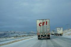 Tunga lastbilar som rusar på iskall motorväg Royaltyfri Bild