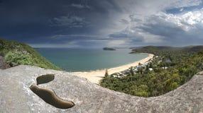 Tunga moln över den centrala kusten Australien för pärlemorfärg strand Arkivbilder