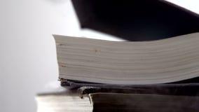 Tunga svarta böcker som faller på vit yttersida stock video