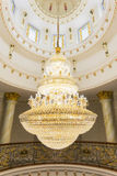 A tungsten bulb crystal chandelier hanging from a ceiling. Stock Images