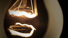 Tungsten filament of electric bulb. Real light bulb turning on, flickering and turning off. Incandescence thread, close up stock video