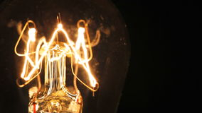 Tungsten filament of electric bulb. Real light bulb turning on, flickering and turning off. Incandescence thread, close up stock video footage