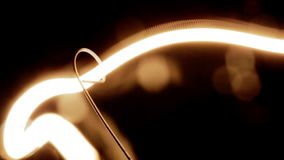 Tungsten filament of electric bulb. Real light bulb turning on, flickering and turning off. Incandescence thread, close up stock footage