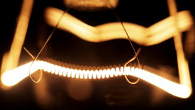 Tungsten filament of electric bulb. Real light bulb turning on, flickering and turning off. Incandescence thread, close up. Loop stock video