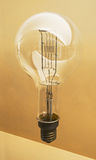 Tungsten large light bulb. Realistic photo image. Light yellow background stock photos