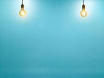 Tungsten light bulb on empty blue wall background. Royalty Free Stock Photo