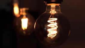 Tungsten light bulb lamps over black background. Concept of light and dark, idea, electricity at modern home. Tungsten light bulb lamps over black background stock footage