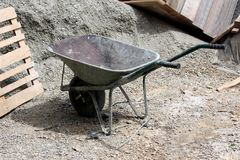 Tungt - använd skottkärrakonstruktionsvagn med två handtag och det enkla hjulet som lämnas på konstruktionsplats royaltyfri foto
