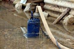 Tungt - anv?nde den gamla delvist doppade metallvattenpumpen som pumpar vatten fr?n ?versv?mmad tr?dg?rd till och med brandslange arkivfoto