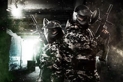 Tungt beväpnad maskerad soldat för paintball två på apokalyptisk bakgrund för stolpe Annonsbegrepp arkivfoto
