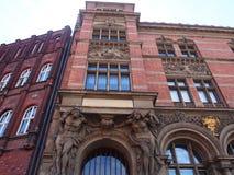 Tungt dekorerade klassiska byggnader i gdansk, Polen r?da tegelstenar, skulpturer och b?gar royaltyfri foto