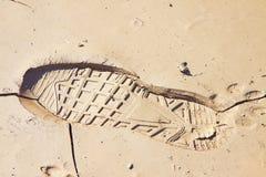Tungt fotspår som lämnas på en lerig sand av en manlig känga royaltyfria foton
