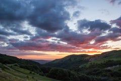 Tungt mörker fördunklar med reflexion av den röda solen under guld- solnedgång fotografering för bildbyråer