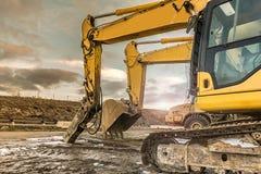 Tungt maskineri i en hård dag av arbete i konstruktionen av en väg arkivfoto
