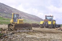 Tungt maskineri på konstruktionen av vägar i bergen arkivfoton