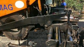 Tungt maskineri som fördelar varm asfalt för att skapa vägyttersida i en romanian liten by stock video
