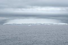 Tungt molnbildande ovanför ett isberg, Antarktis royaltyfri bild