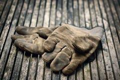 Tungt slitet ut och funktionsdugliga handskar för bortskämd konstruktion på en gjuten trätabell royaltyfri fotografi