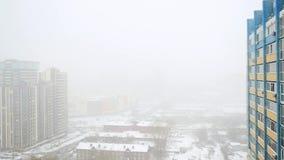 Tungt snöfall i staden i slowmotion Snöig gator, hus och maskin Ändringsfokus på suddigt 1920x1080 arkivfilmer