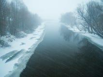 Tungt snöfall på floden royaltyfri bild