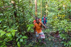 Indonesian Papuan hunter walking in jungle Stock Photo