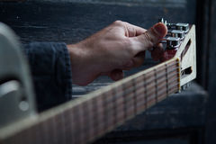 Tuning an acoustic guitar on dark background. Caucasian male hand tuning an acoustic guitar on black dark wooden background with selective focus Royalty Free Stock Photography
