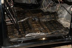 Tuning the car in a sedan body with three layers of noise insulation of the front floor part. Audio and vibration isolation. Soft. Material. Dismantled car royalty free stock images