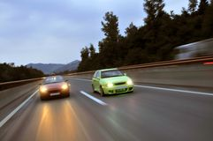 Tuning cars racing down the highway. Sport fast tuning cars speeding on highway captured with long exposure Stock Images