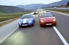 Tuning cars racing down the highway Royalty Free Stock Photo