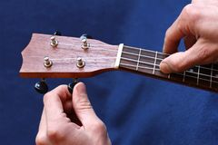 Tuning the first string of ukulele, closeup. Tuning the first string of ukulele, human hands, closeup Stock Image