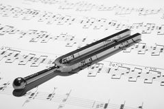 Tuning fork on sheet music Stock Image