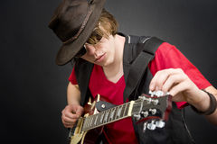 Tuning a guitar. A cool looking guitar player tuning his instrument Royalty Free Stock Photos