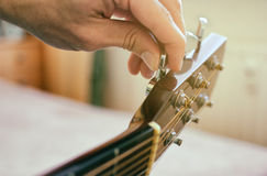 Tuning the guitar. Fingers are turning the tuning peg on the head of acoustic guitar. Authentic shot with blurred room in the background stock photo