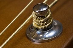 Tuning head machine of acoustic guitar with metall strings. Detail of tuning head machine of acoustic six-strings guitar close-up Royalty Free Stock Photos
