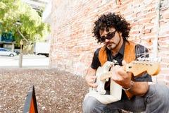 Tuning his guitar Royalty Free Stock Photos