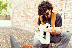 Tuning his guitar. A street musician tuning his instrument Royalty Free Stock Photography