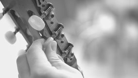 Tuning an old acoustic guitar. Fingers turning the tuning pegs and gears of the headstock of a acoustic guitar. Black and white footage stock video footage