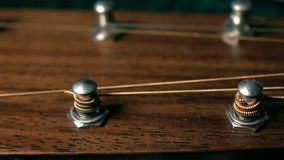 Tuning pegs of acoustic guitar. Tuning or adjustment concept. 4K close up dolly video. Tuning pegs of acoustic guitar. 4K close up dolly shot stock footage
