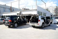 Tuning two car in a SUV white and black body with three layers of noise insulation with opened doors and trunk standing outdoor. туффк the stock photos