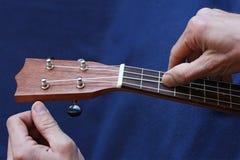 Tuning the ukulele strings, closeup. Tuning the ukulele strings, human hands, closeup Stock Images