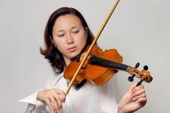 Tuning Violin. Girl tuning violin isolated silhouette on gray background. Half korean half european gilr stock photos