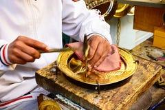 Tunis Medina Artisan, Golden Metalworking, Tunisia. Tunisian artisan working a golden plate with nail and small hammer, Tunis Medina, Tunisia Stock Image