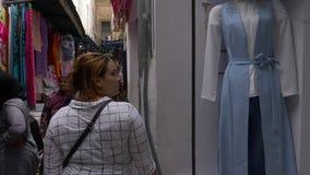 Tunis, Tunesien - 6. Juni 2018: Arabische Frau, die auf traditionelles souk in alter Medina-Stadt geht Leute, die auf Araber kauf stock video