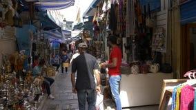 Tunis, Tunesien - 6. Juni 2018: traditioneller arabischer Markt auf schmaler Straße in alter Medina-Stadt Touristische Leute, die stock footage